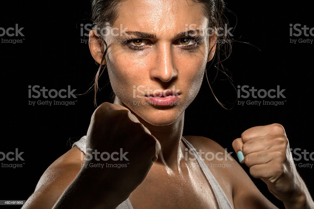 Tough chick powerful strong fighter boxer MMA piecing intense eyes stock photo