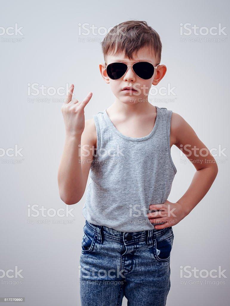 Tough child making symbols with hand stock photo