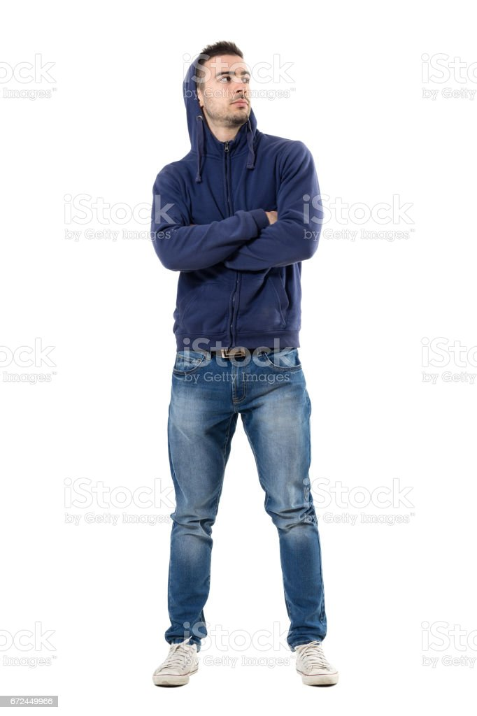 Tough confident young man with hoodie on head and crossed arms looking up stock photo