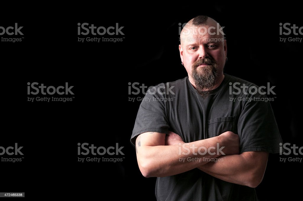 tough guy with arms crossed and mohawk hairstyle stock photo