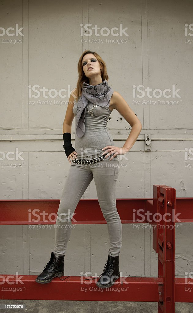 tough looking girl in industrial setting stock photo