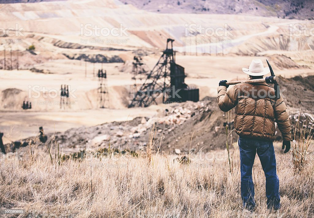 Tough man stands in rock quarry with old oil drill royalty-free stock photo
