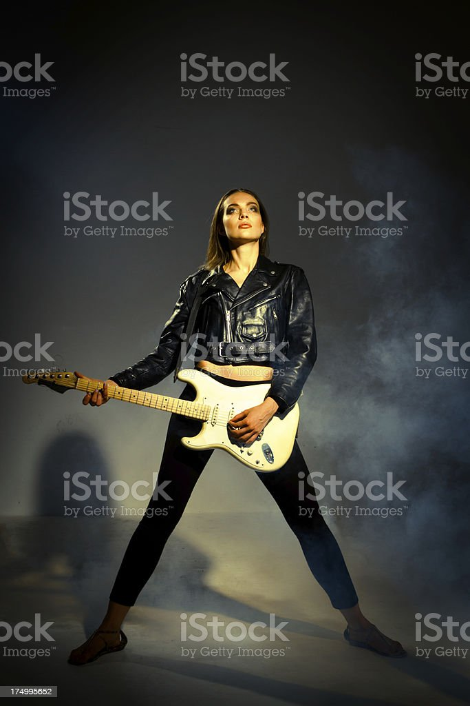 Tough rocker chick holding her guitar royalty-free stock photo