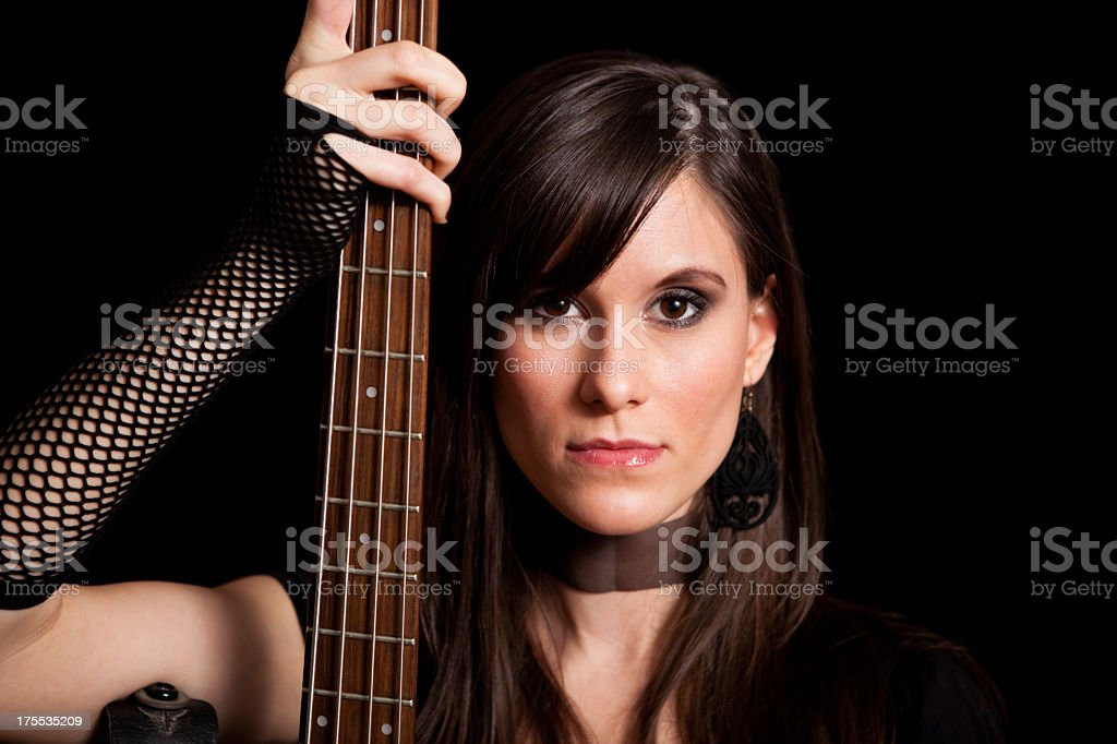 Tough Rocker Girl Holding Bass Guitar, With Black Background royalty-free stock photo