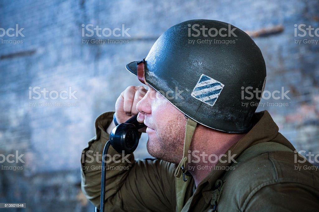 WW2 tough sergeant GI holds field telephone  in dark building stock photo