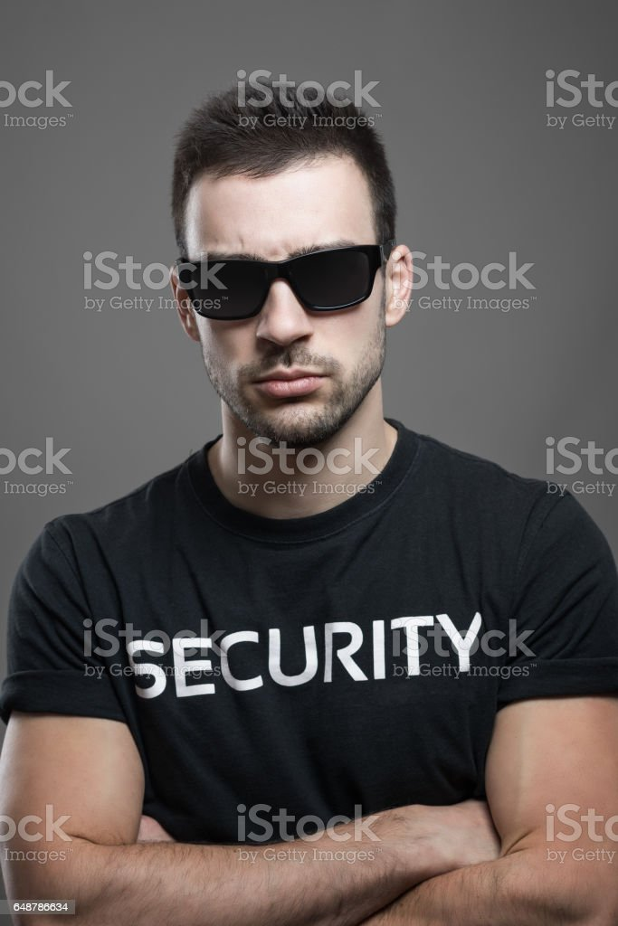 Tough serious male security guard with sunglasses and crossed arms stock photo