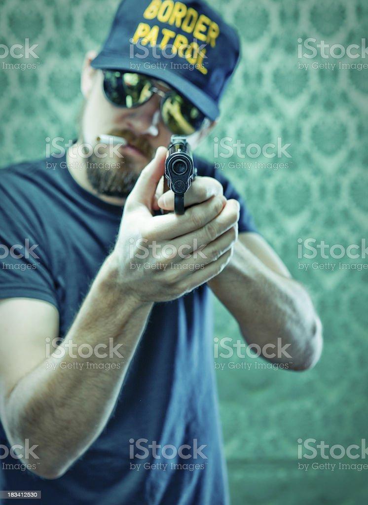 tough smoking Border Patrol Police Man aiming Pistol Gun royalty-free stock photo
