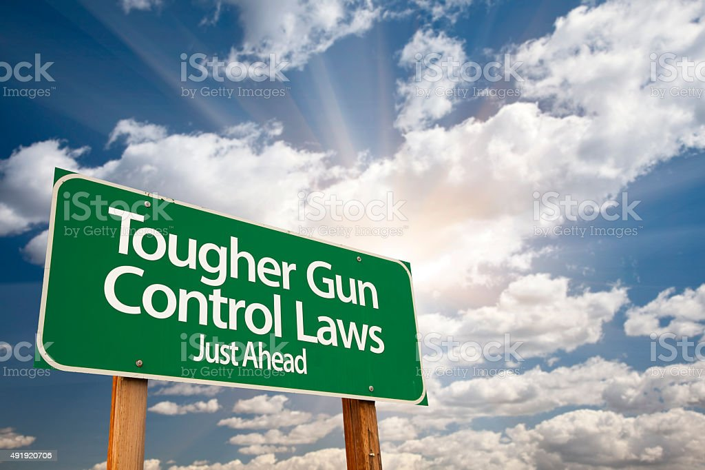 Tougher Gun Control Laws Green Road Sign Over Clouds stock photo