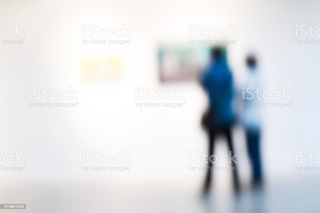 touist watching paintings in a museum stock photo