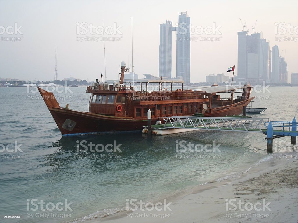 Tour boat moored in Abu Dhabi Harbor, highrises stock photo