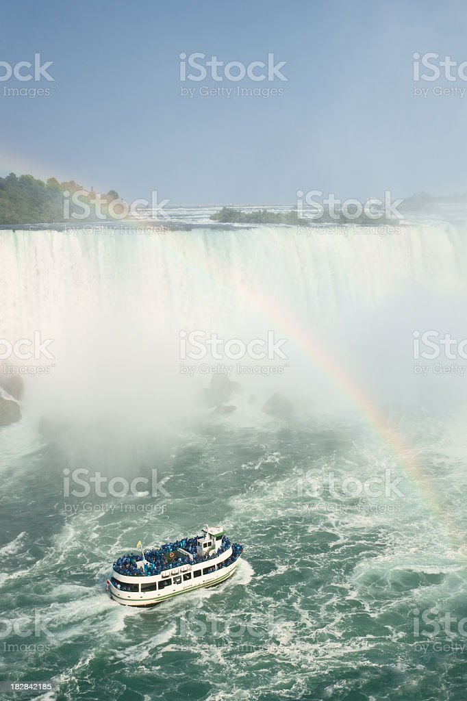 Tour boat under rainbow at Niagara Falls. stock photo