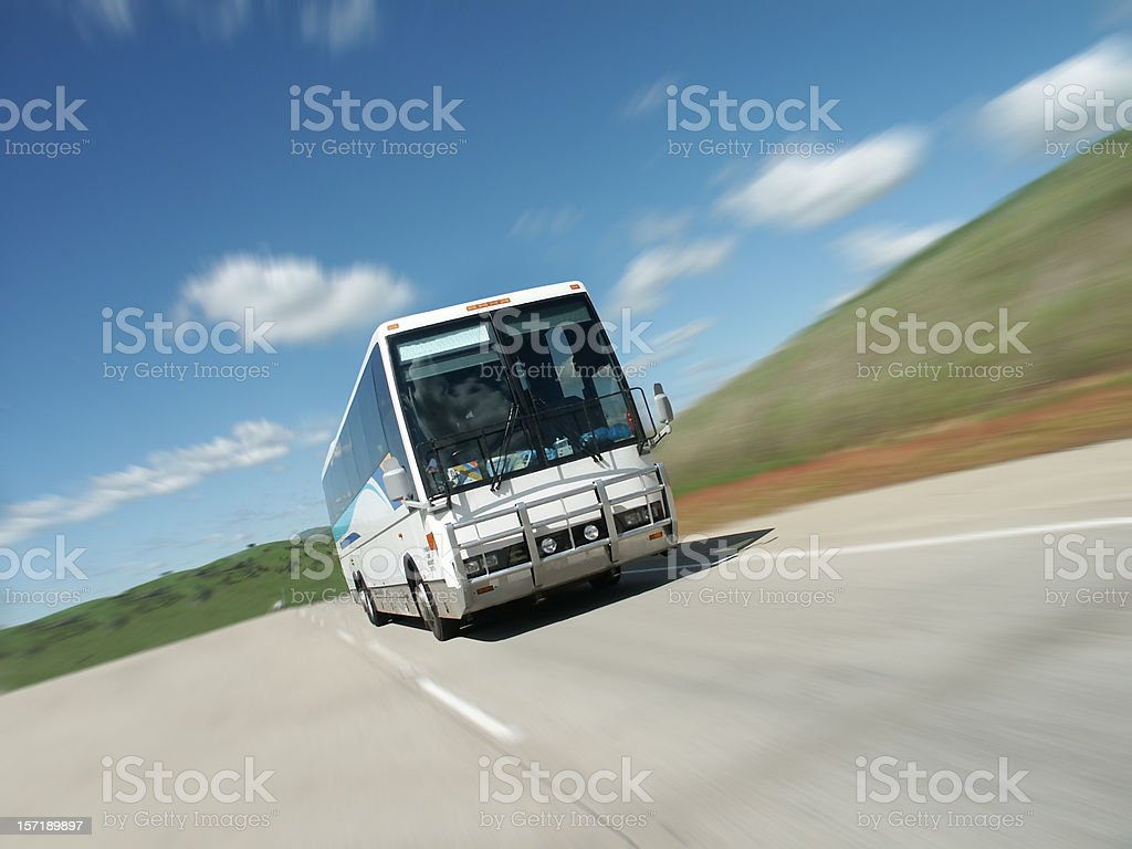 Tour bus speeding down empty highway royalty-free stock photo