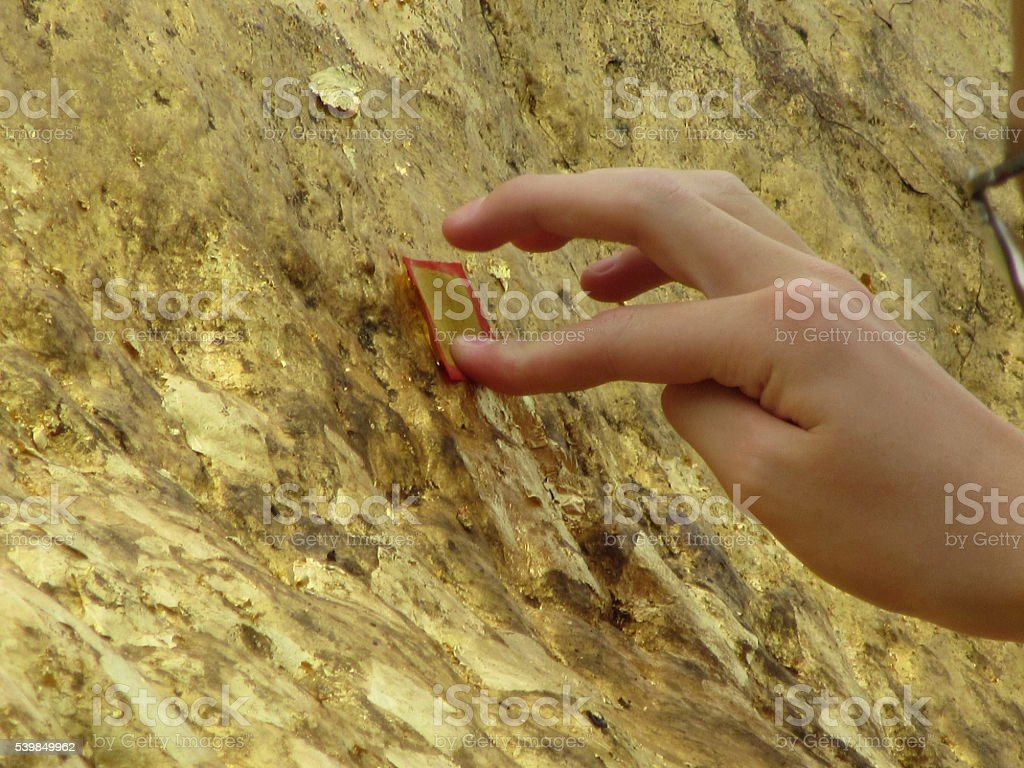 Tourist adding Gold Leaf to Golen Rock, Myanmar stock photo
