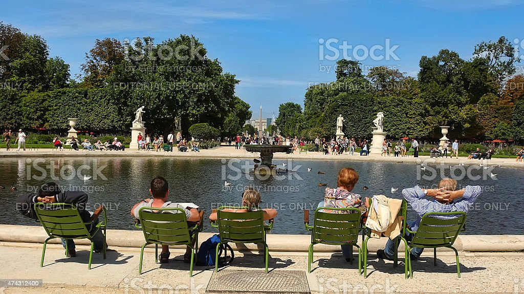 Tourist and Parisians rest in Tuileries garden near Louvre museum. stock photo