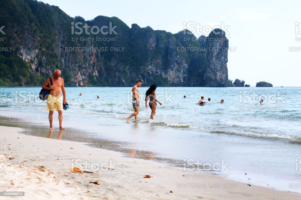 Tourist and thai woman going into Andaman sea stock photo