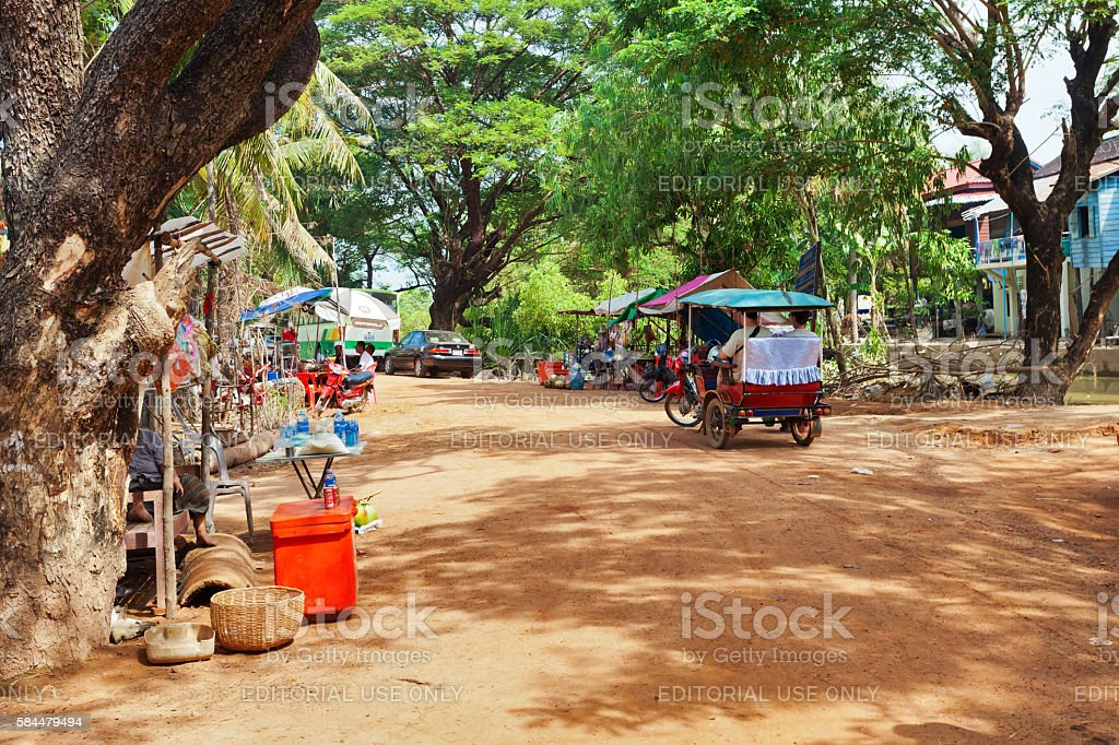 tourist arriving by tuk-tuk in village near Tonlesap lake. stock photo