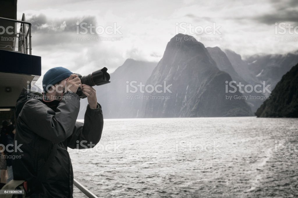 Tourist at Milford Sound in Fiordland National Park, New Zealand stock photo