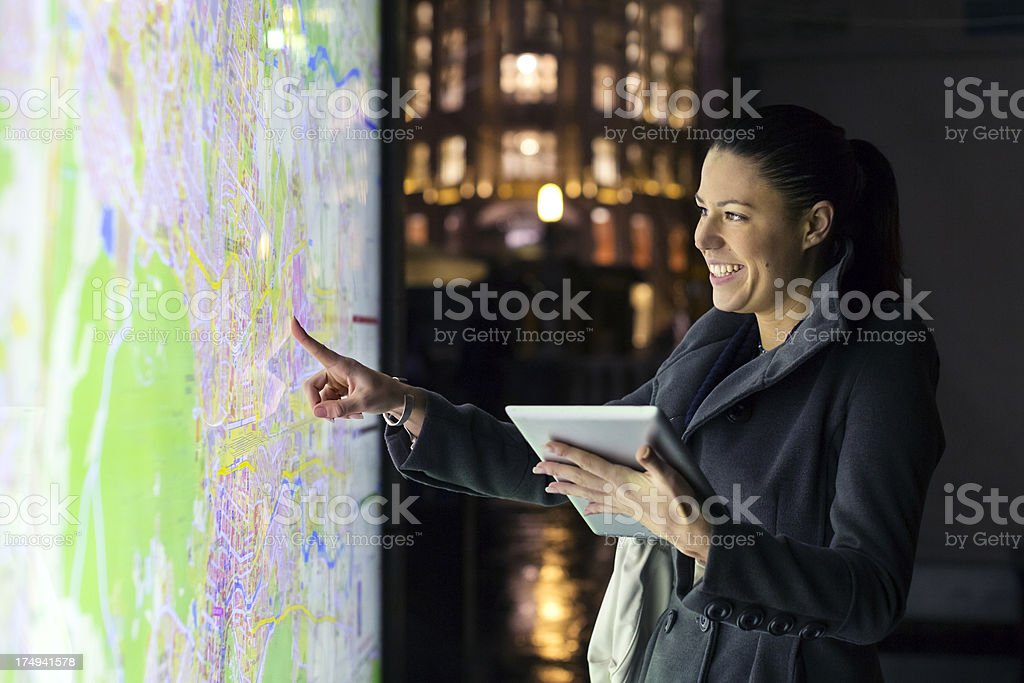 Tourist at night pointing on the map using digital tablet stock photo