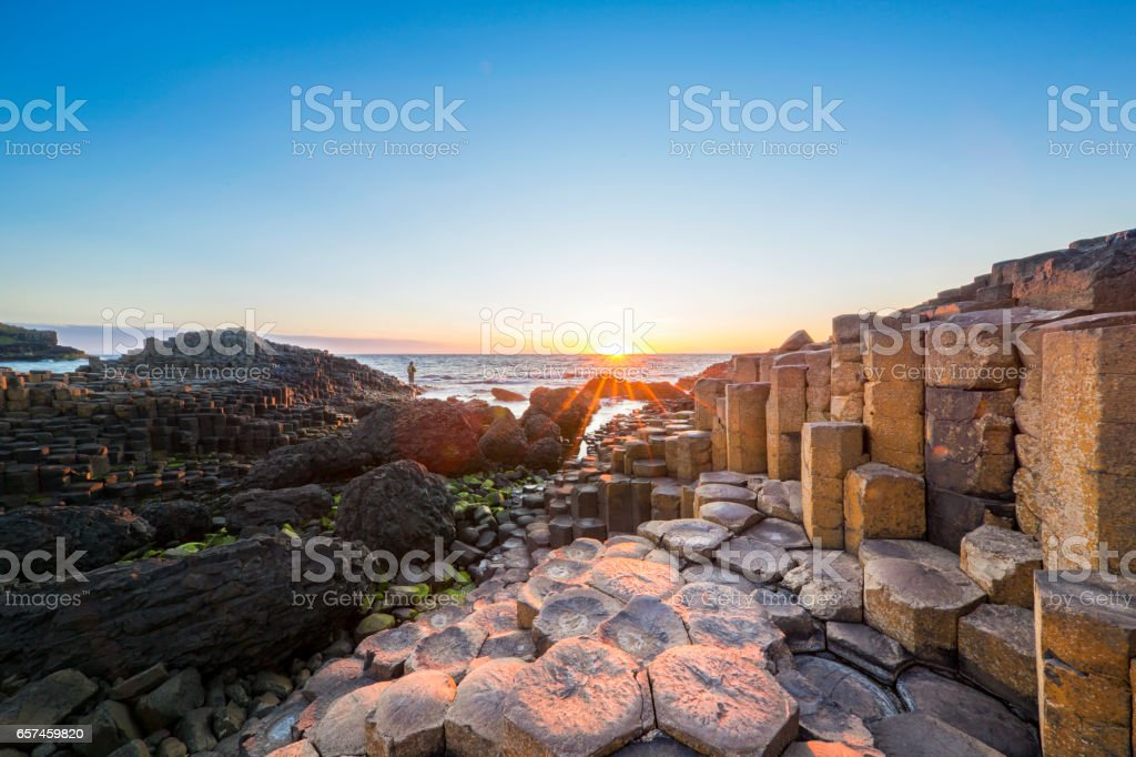 Tourist at Sunset over Giants Causeway, Northern Ireland stock photo