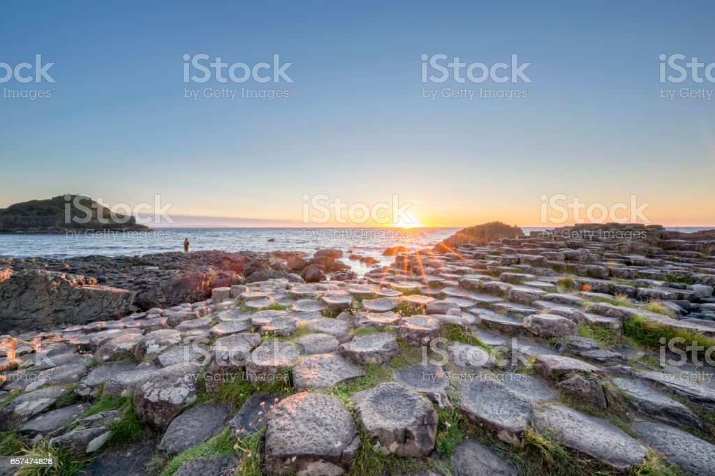 Tourist at Sunset over Giants Causeway, Northern Ireland stock photo