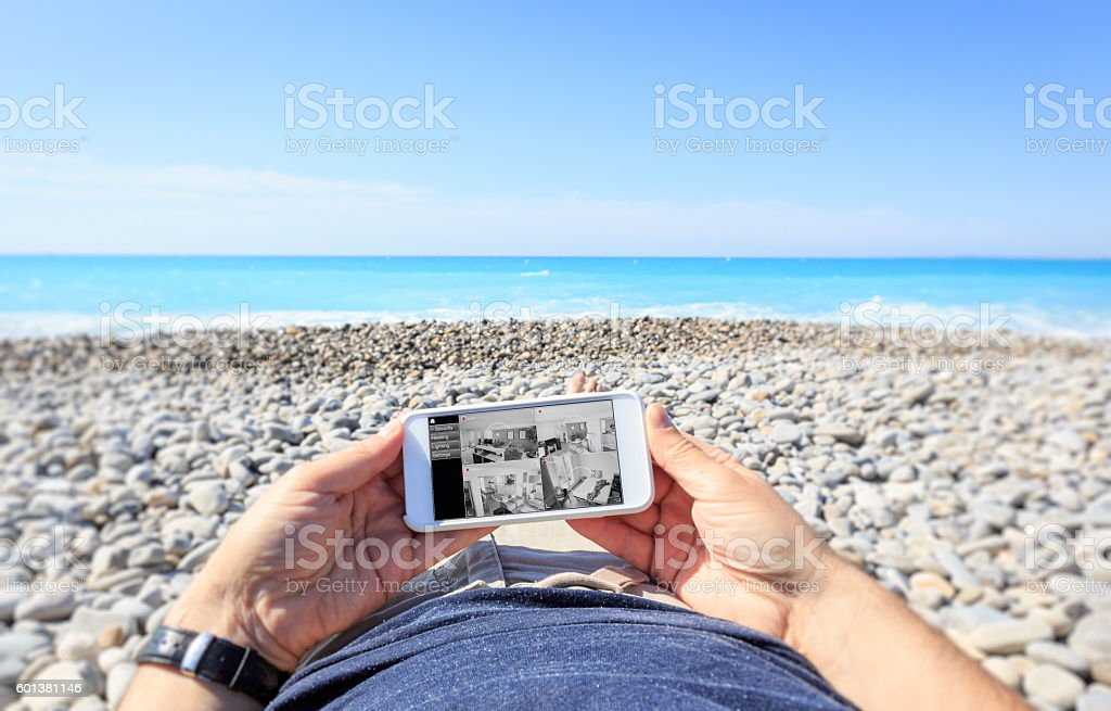 Tourist at the beach checking surveillance cameras at home stock photo
