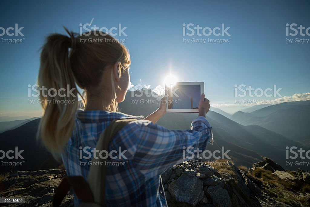 Tourist at top of mountain taking picture with digital tablet stock photo