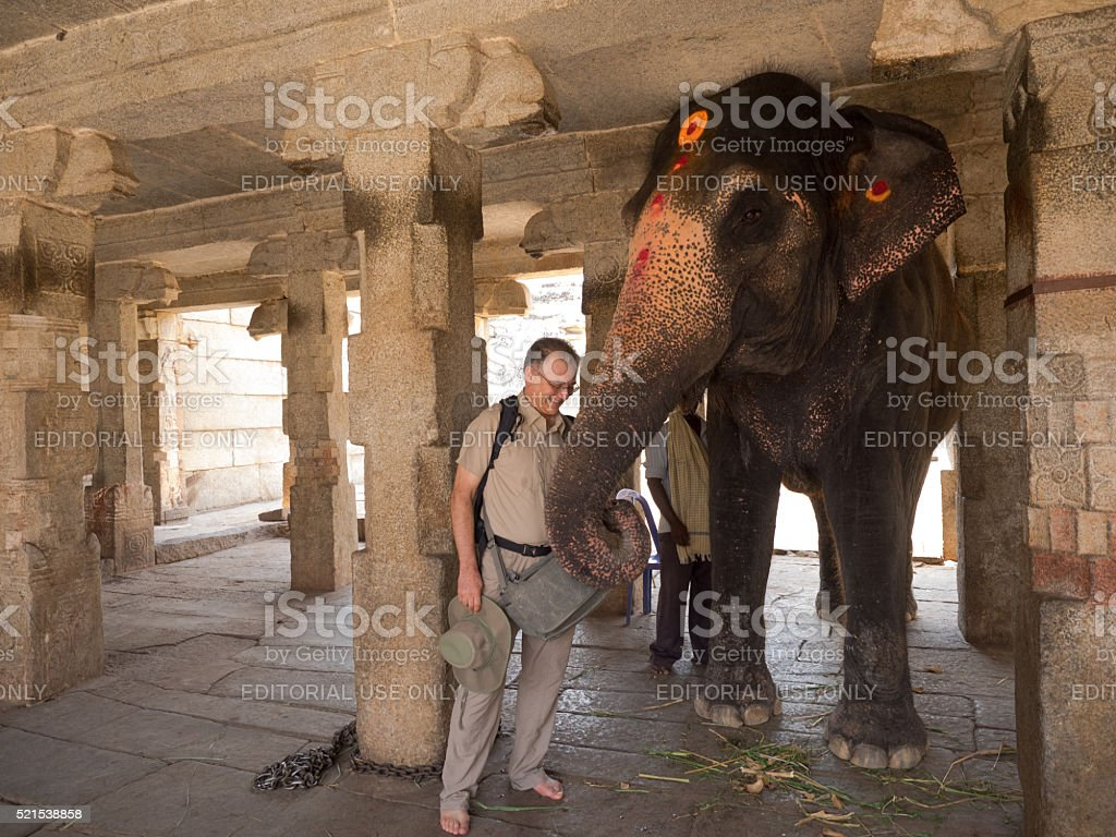 Tourist being blessed by Indian elephant in Virupaksha Temple, Hampi stock photo