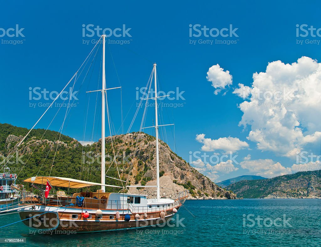 tourist boat moored at bay surrounded by mountains stock photo