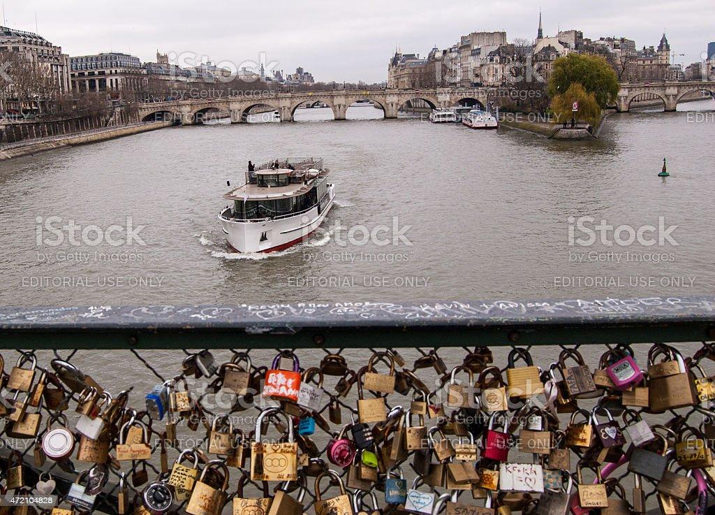 Tourist boat passes near Love Locks bridge in Paris, France. stock photo