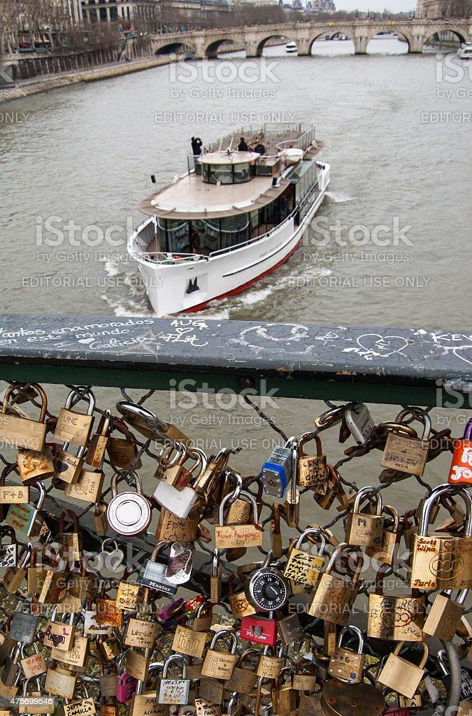 Tourist boat passes near love locks bridge in Paris stock photo