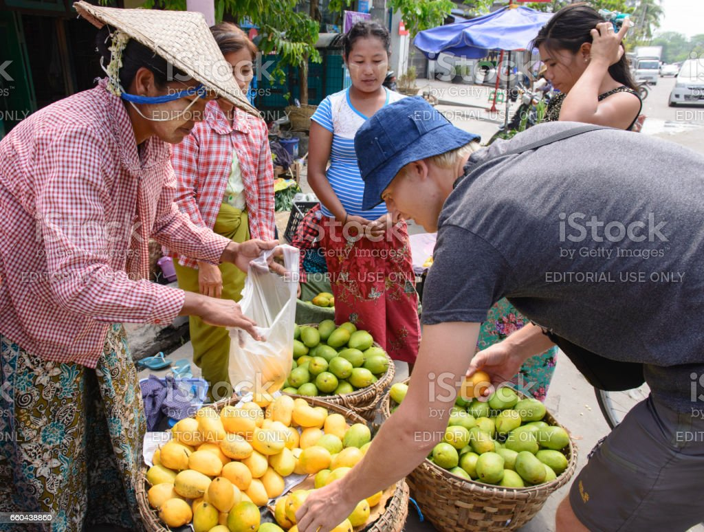 Tourist buying ripe fruits on the street market in Burma stock photo