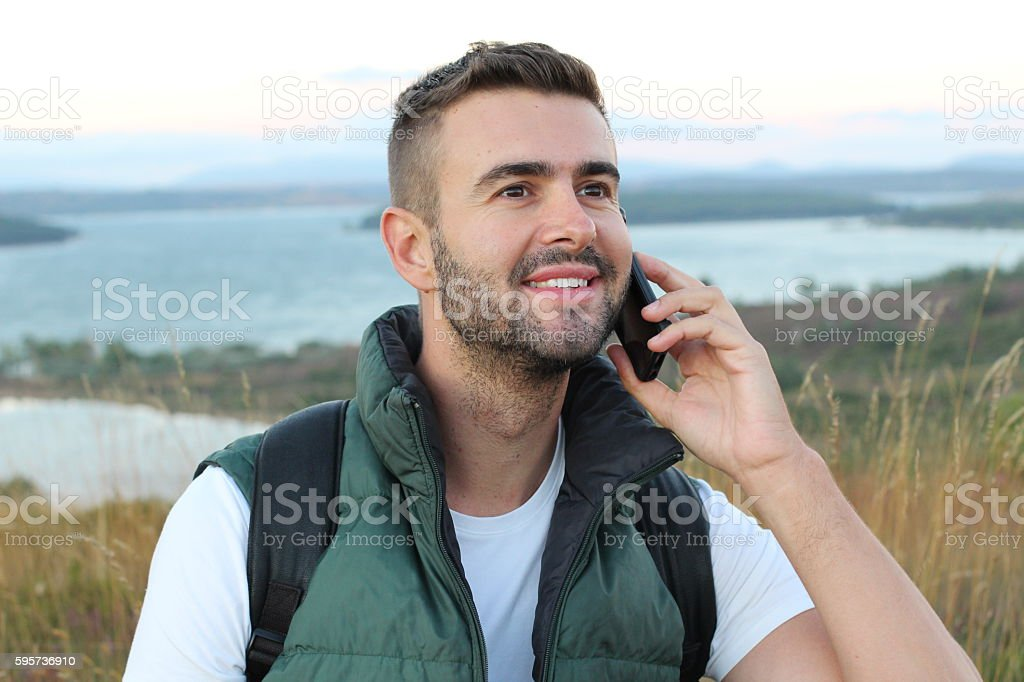 Tourist calling by phone phone in the mountains stock photo
