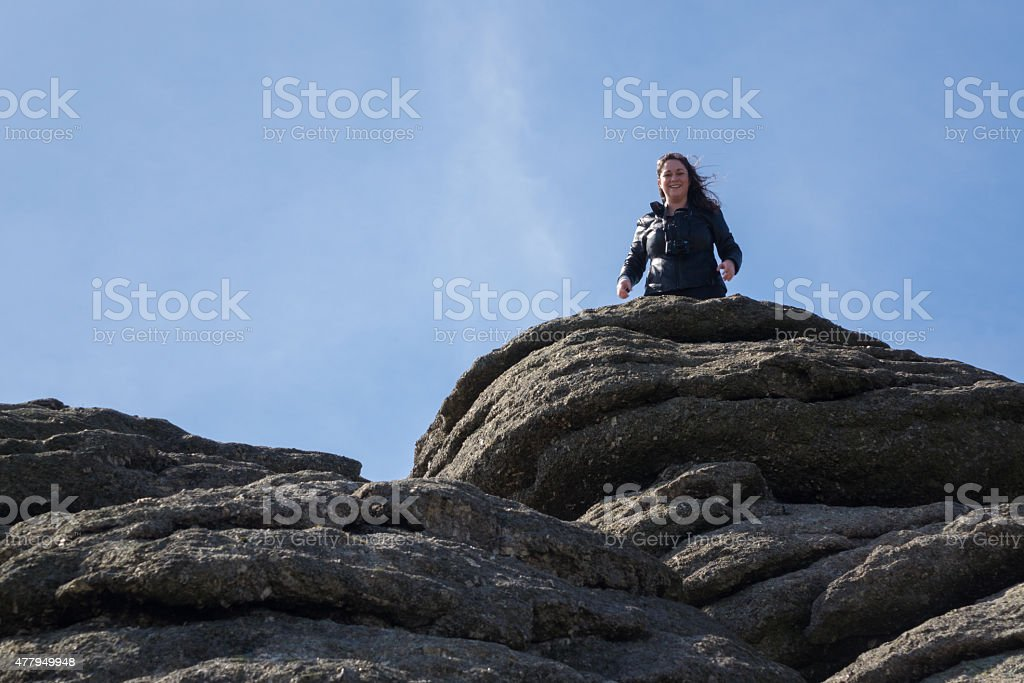Tourist climbs up the granite slopes of Haytor Rocks stock photo