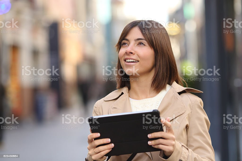 Tourist consulting guide in a tablet and watching the street stock photo