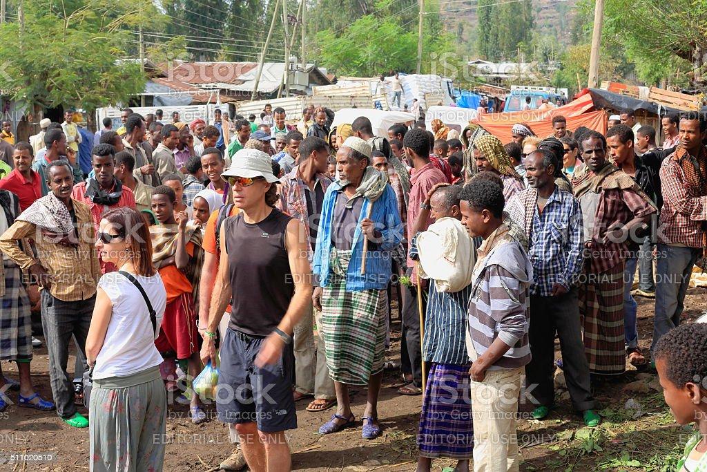 Tourist couple among locals. Degan town-Ethiopia. 0101 stock photo