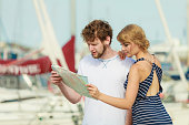 Tourist couple in marina looking up directions on map