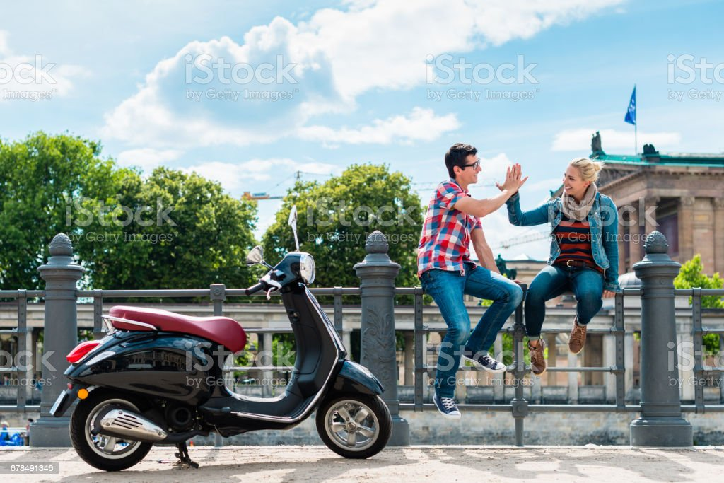 Tourist couple making stop during Vespa excursion in Berlin stock photo