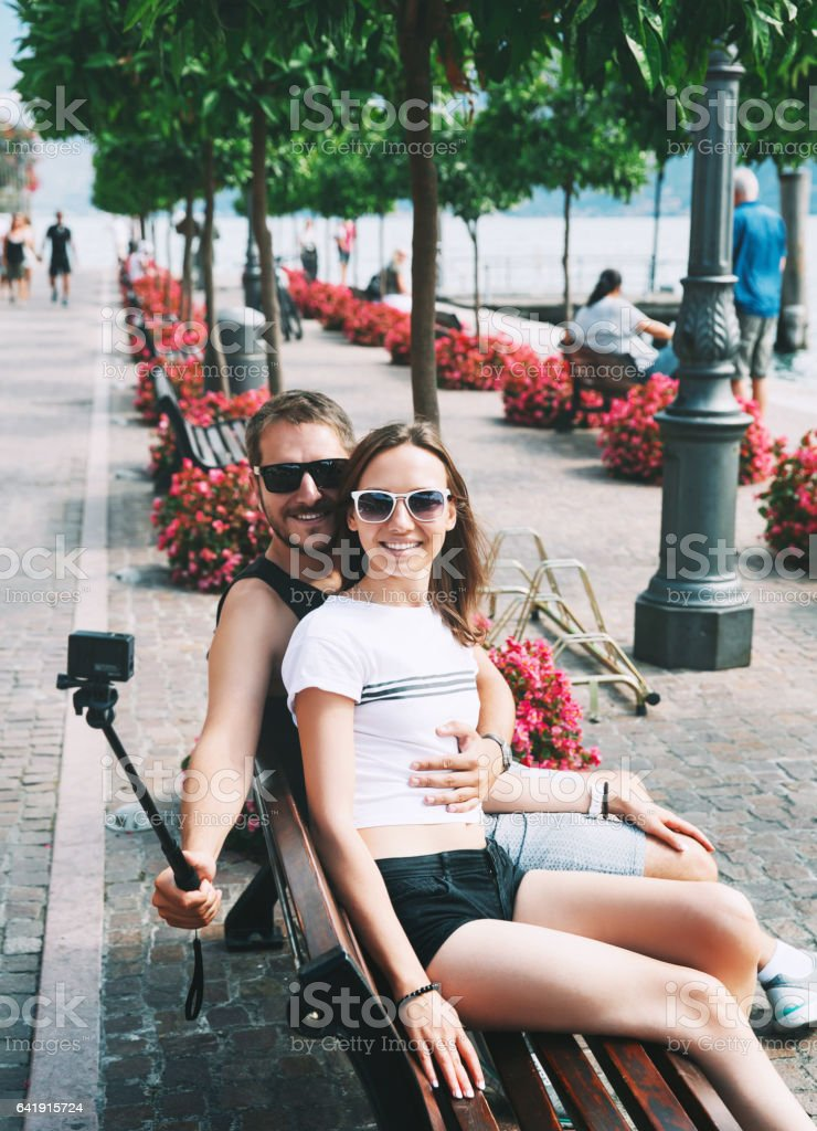 Tourist, couple of lovers making selfie photo on motion camera at Lake Garda, Italy, Europe. stock photo