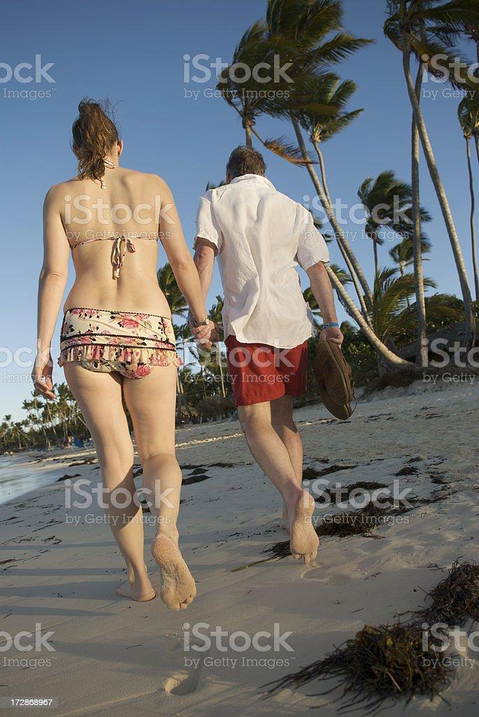 Tourist Couple Takes Sunset Walk Along Natural Beach royalty-free stock photo
