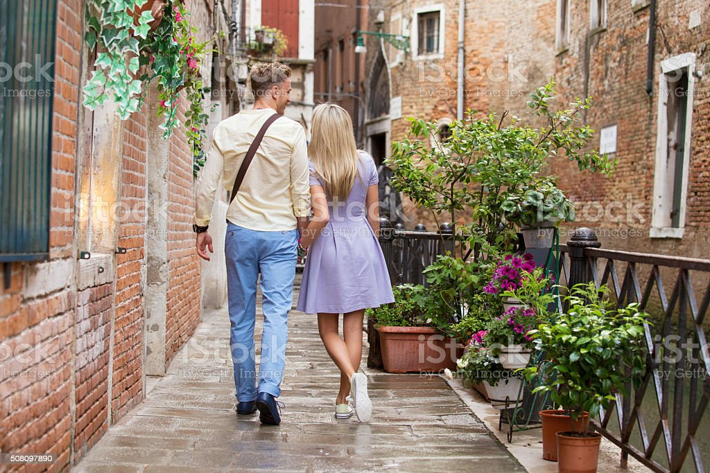 Tourist couple walking in romantic city stock photo