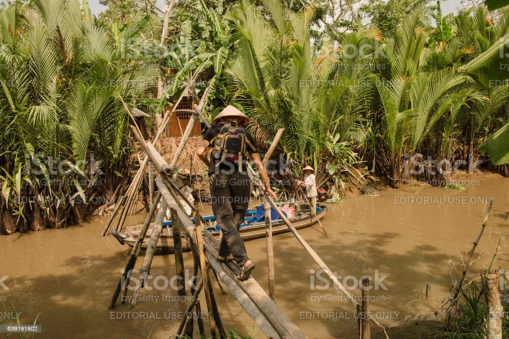Tourist crossing wooden bridge over small canal of Mekong delta stock photo