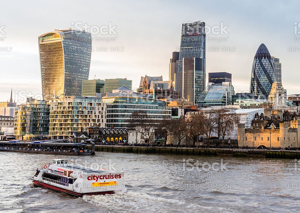 Tourist cruiser by Thames passing The City and the Tower stock photo
