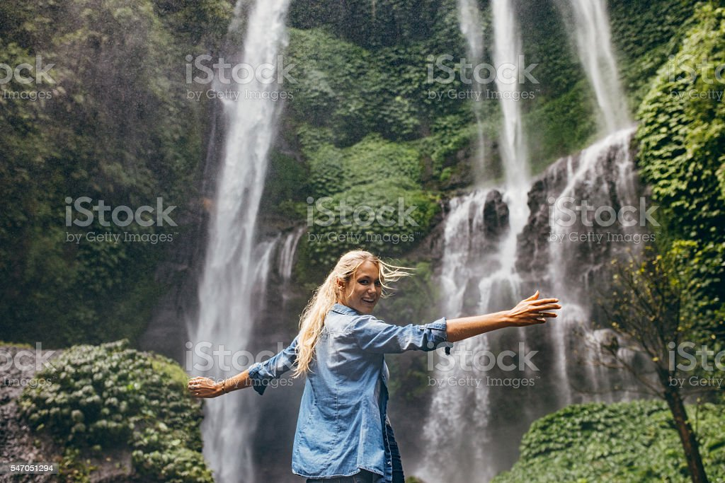 Tourist enjoying by a waterfall in forest stock photo
