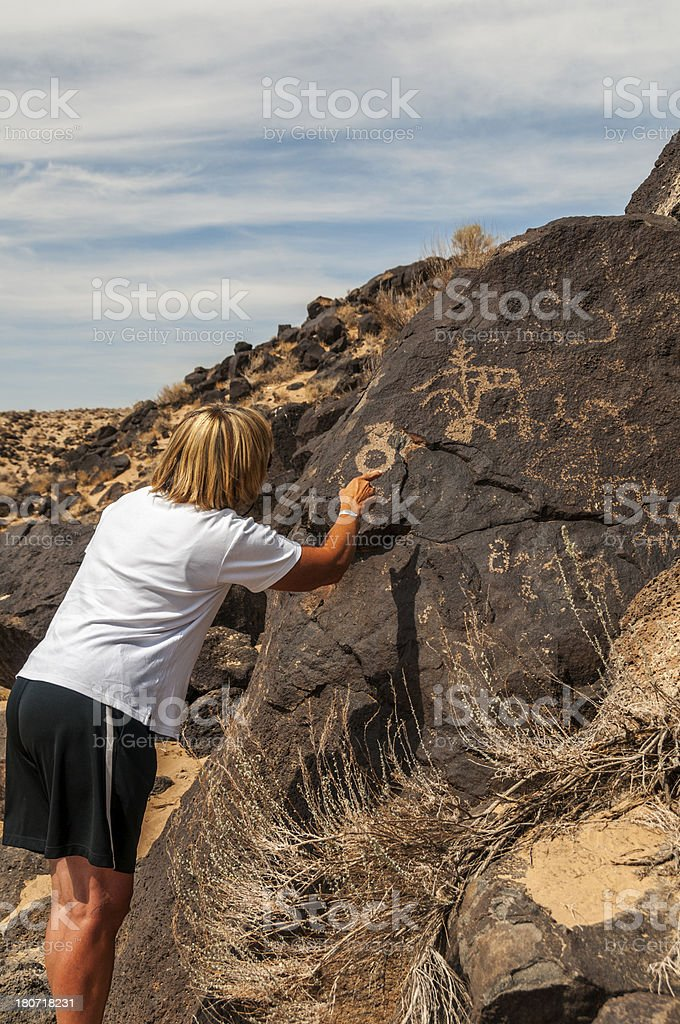 Tourist Examining Petroglyphs stock photo