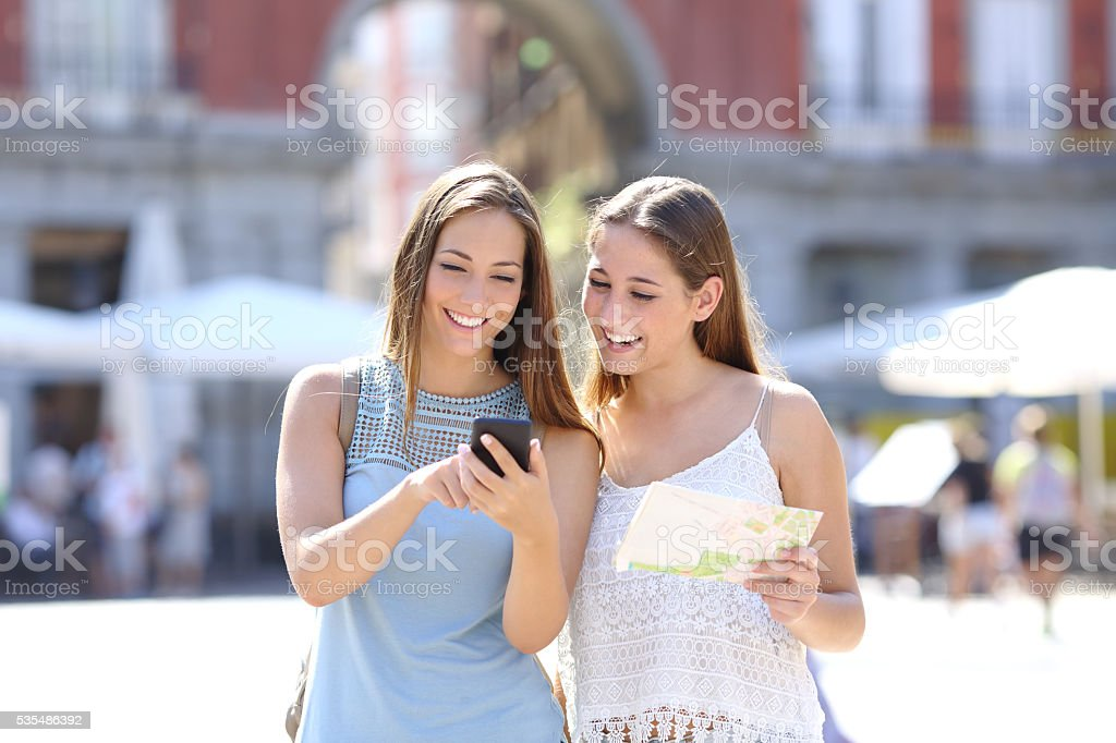 Tourist friends consulting an online guide stock photo
