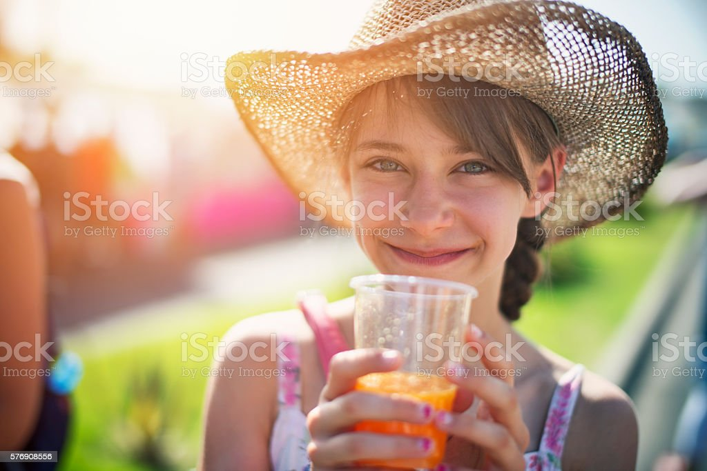 Tourist girl drinking a glass of freshly squeezed orange juice stock photo