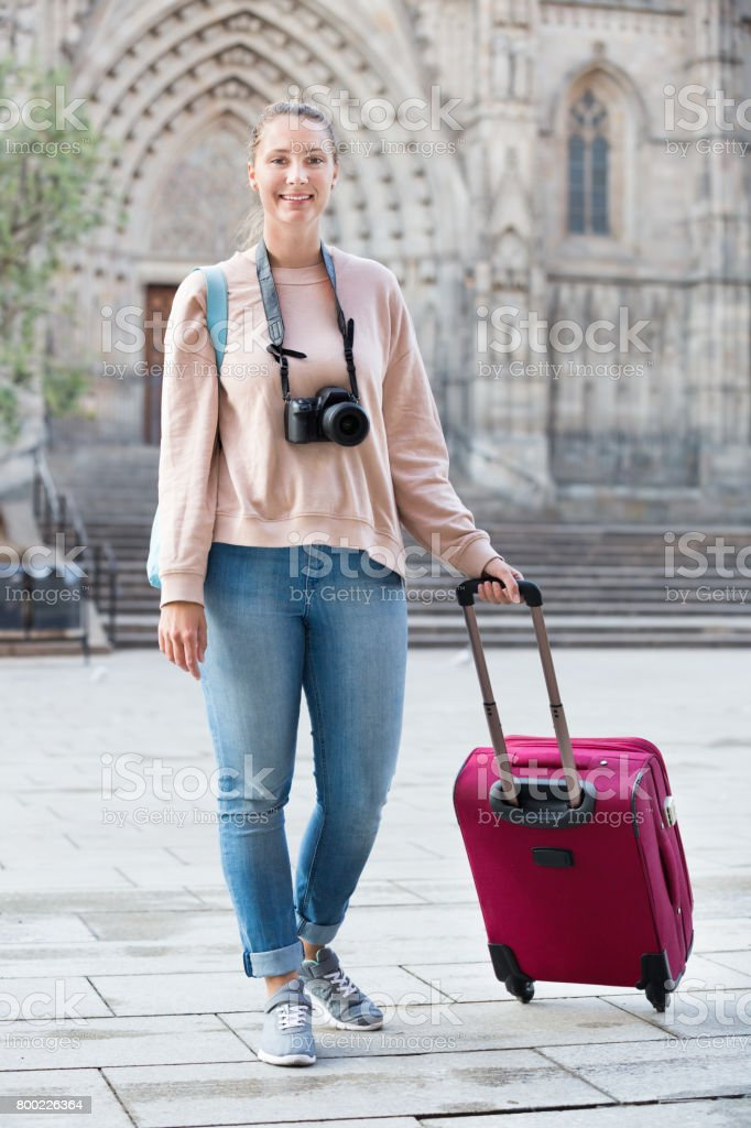 Tourist girl taking a walk with travel bag stock photo