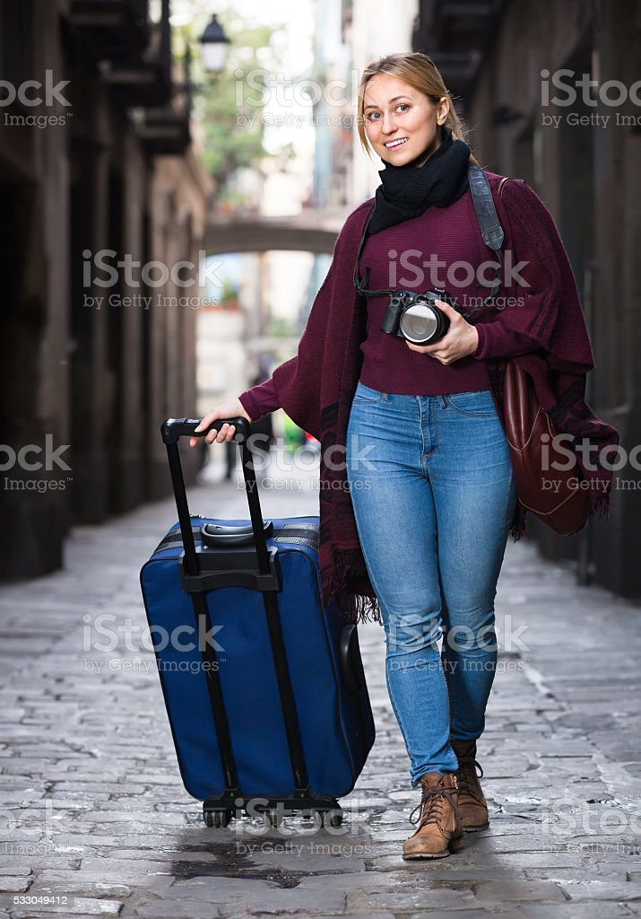 Tourist girl walking with the travel bag stock photo