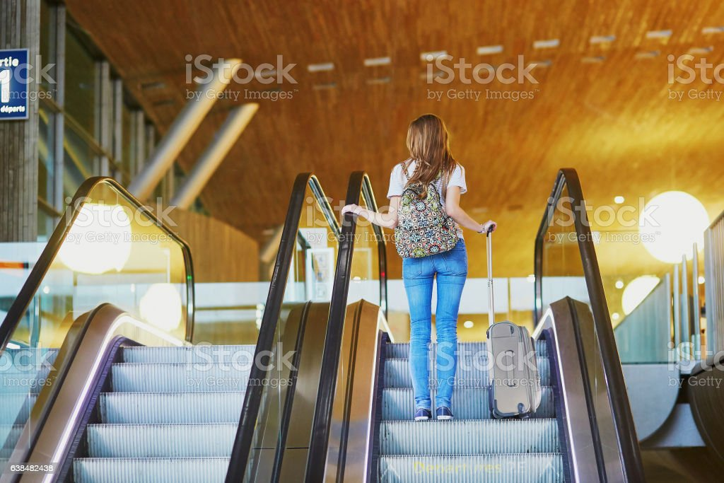 Tourist girl with backpack and carry on luggage on travelator stock photo