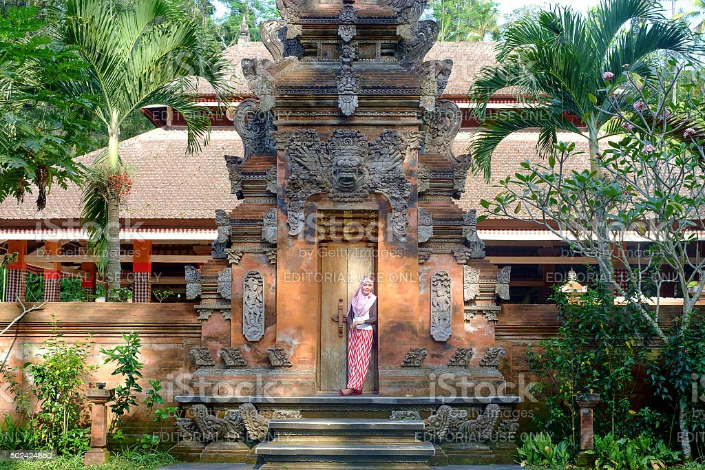 Tourist giving a post in the temple at ubud. stock photo